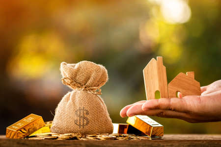 Man hand hold home model with presenting and money bag put on the gold bar and coin with growing interest in the public park, Saving money for buy house or loan for investment of real estate concept.