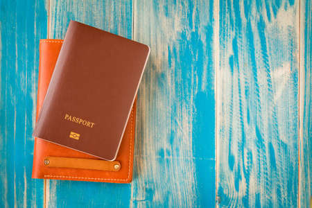 Passport and a brown leather wallets put on the vintage blue background for travel planning concept.
