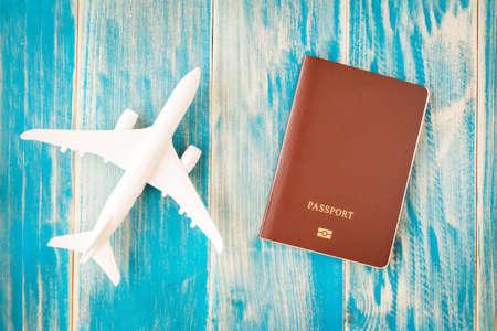 Passport and a plane model put on the vintage blue background for travel planning concept. Reklamní fotografie