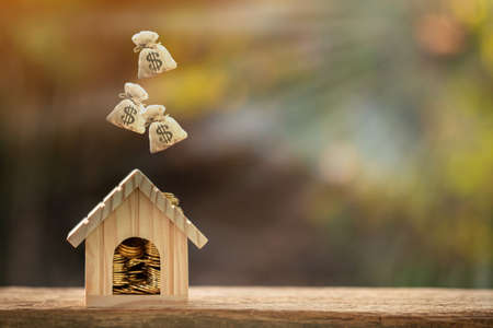 Home model and gold coin and dropping money bag on the top put on the wood in the public park, Saving money for buy a house or loan for plan business investment of real estate concept.