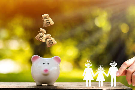 Woman hand holding a family with paper cut to piggy bank with dropping money bag on the top with working capital management in the public park, Saving money for future investment concept. Stock fotó