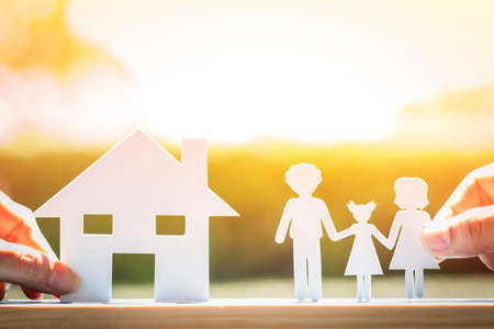 Woman hand hold a family and home with paper art on sunlight in the public park, for love concept,