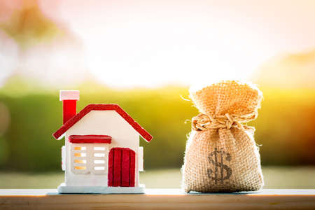 Money bag and house model put on the wood on sunlight in the public park, for Business investment loan or for save money for buy a new real estate concept.