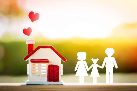 Home model and red heart on the top and family with paper art put on the wood on sunlight in the public park, For love concept.
