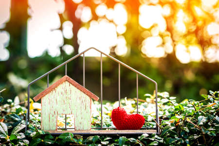 Home model and red heart put in the shelf with shape house on grass for Business investment loan or buy for real estate concept, on sunlight in the public park.