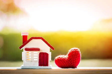 Home model and red heart put on the wood on sunlight in the public park, For family love concept.