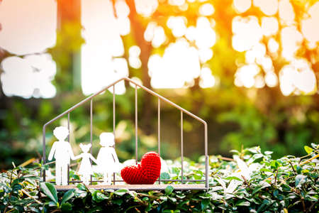 A family with paper art and red heart put in the shelf with shape home on grass for love concept, on sunlight in the public park.