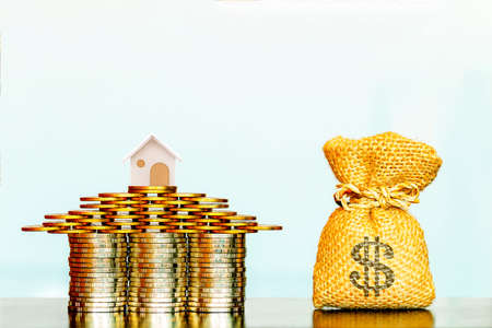 Stacking gold coins and home model put on the top as destinations and money bag on the desk in the office, Loans for real estate or buy a new house in the future concept.