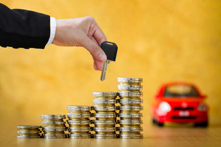 Investor hand hold a car key submit to each other a car model and Stacked gold coin with growing interest in the office, The buying for ownership of a chattel concept. Stock Photo