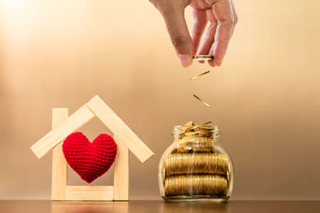 Investor's hands saving gold coin into the bottle bank loaded with grow interest and red heart in the middle of the wooden house model on brown background, Business investment for real estate concept.