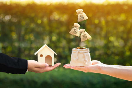 Businessman and woman hand holding a model home and money bag presenting to each other in the public park, Saving money for buy a new house or loan for plan business investment of real estate concept.