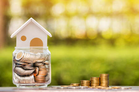 Home model put in the bottle and stack gold coin with growing of savings money put on the table in the public park, Loan for buy house and real estate for business investment concept.