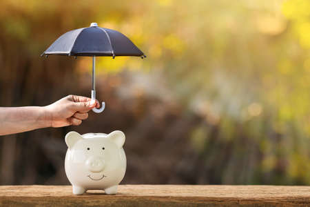 Piggy bank and woman hand hold the black umbrella for protect on sunlight in the public park, to prevent for asset and saving money for buy health insurance concept. Imagens