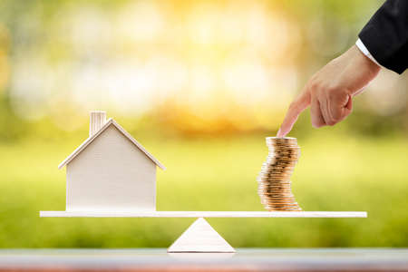 Businessman point hand to the stack gold coin with recommend an investment goal of the victory for ones success and home put on the scales in the public park, Real estate business investment concept.