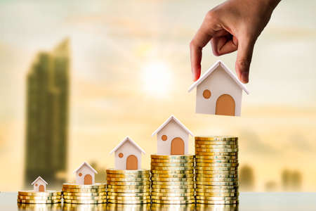 Investor hand hold a home model put on the stack coin with growing on photo blur cityscape on sunlight background, Savings money for buy house and loan to business investment for real estate concept.
