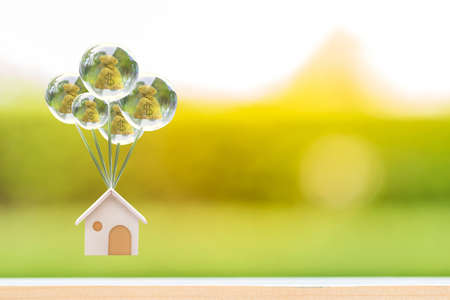 Home model hanging a beautiful crystal balloon with money bag stay inside with soar in the public park, Saving money for buy a new house or loan for plan business investment of real estate concept.