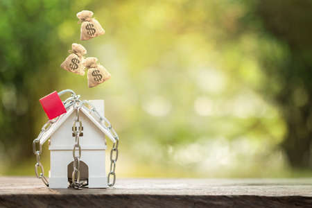 Home model with security and lock and dropping a money bag on the top in public park, Business investment for real estate and or loan for buy house concept.