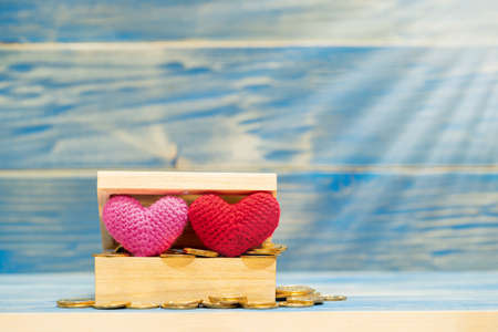 Red and pink heart is made with yarn and gold coin in the wooden box on the vintage blue background, Saving money for buy health insurance to the loved ones concept.