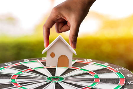 Woman hand hold for select a home model on dartboard as destination on sunlight, Loan for asset or saving money for buy a new real estate to family in the future concept. Stock Photo