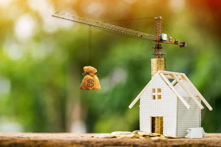 Home with stack gold coin with growing interest value and tower crane with money bag in the public park, Saving for buy house or loan for business investment with construction the real estate concept.
