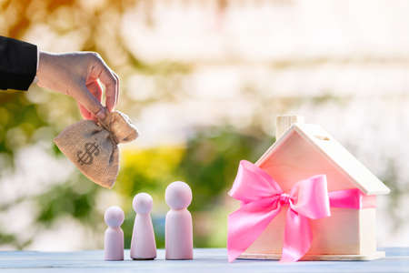 Business man hand hold money bag for select or give to home model tied with pink ribbon and wood family on bokeh in the public park, The buy new house or real estate as gift to the one loved concept.
