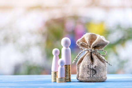Family put on the gold coin and money bag with growing value put on the vintage blue wooden board in the public park, Saving money for planning business investment in the future concept.
