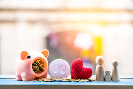 Stacking coins and piggy bank and wooden family and red heart put on the wood on the morning sunlight in public park, Saving money and loan for business investment concept. Banque d'images