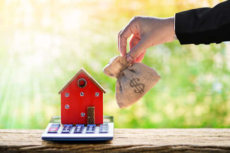 Businessman hand holding money bag presenting to the red home model put on the calculator put on the wood in the public park, Saving money for buy house or loan for investment of real estate concept. Foto de archivo