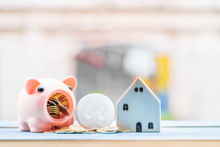Piggy bank and gold coin with working capital management and home model is destination put on the blue vintage wood board, Loan and business investment with real estate for future concept.