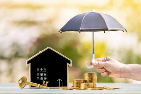 Blackboard house and stacked gold coin and master key and woman hand hold the black umbrella for protect on sunlight in the public park, Saving money for real estate and property protection concept.