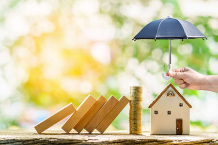 Collect gold coin and woman hand hold open the black umbrella for protect the home from hazard falling wood block in the public park, Saving money for buy insurance of real estate concept. Imagens