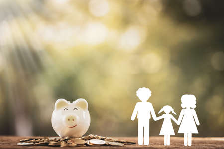 Family with paper cut and piggy bank put on the gold coin with growing value in the public park, Saving money for planning business investment in the future concept.
