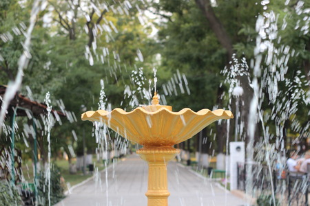 light green background: Yellow fountain in the drops of water in the park