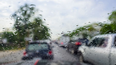 Car windshield in traffic jam and during rain,steering wheel,many cars