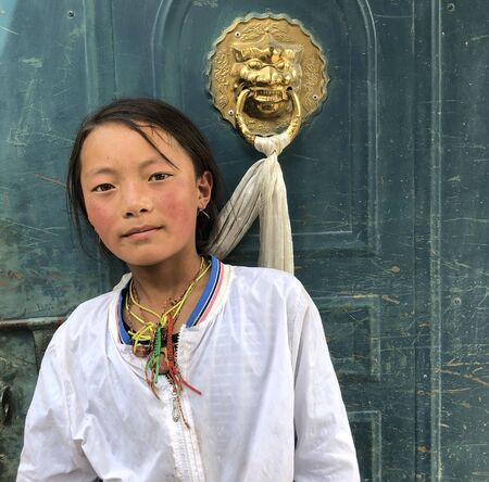July 21,2018 Gansu,China Tibetan children are standig on the door and looking at cameras in the provinces countryside 에디토리얼