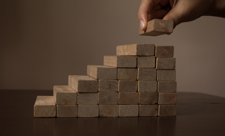 Hand arranging wood block stacking as step stair on wooden table. Business concept for growth success process. Copy space Banco de Imagens