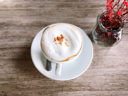 Hot Coffee in a white cup on marble table and flowers vase in Coffee shop top view