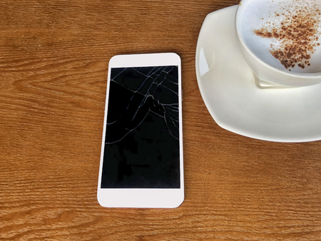 Mobile cracked tuchscreens for communications is brocken placed on a wooden table and coffee mugs in coffee shop