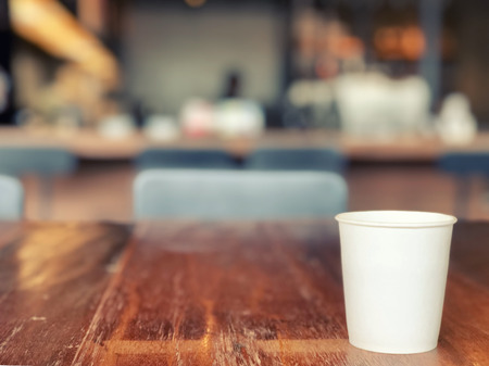 a white paper glass placed on a wooden table in a coffee shop, bokeh background and texture