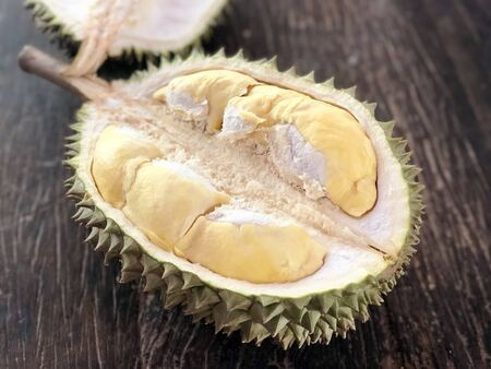 Durian,yellow piece of durian with green and brown peel on wooden table , the most  fruit in South East Asia especially Thailand. Also known as the King of Fruits.