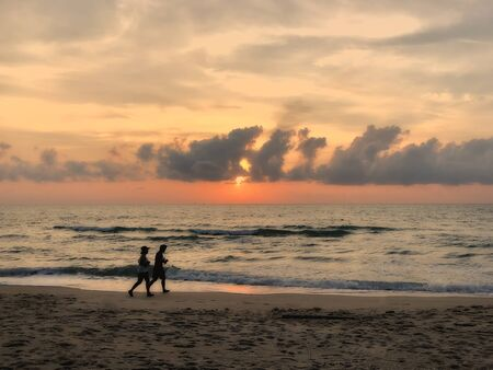 man and woman couple running joking on the beach on sunset twilight sky silhouette on April 07,2019 in Khanom beach ,Thailand Standard-Bild - 132098631