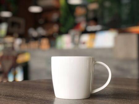 biały kubek do kawy na stole w kawiarni z kolorowym rozmytym tłem