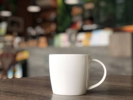 white coffee mug on the table in the cafe shop with colorerful blurred background