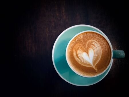 Coffee  Latte with Heart Design in green cup on wooden table in cafe with lighting background Top view  on a rough textured wooden surface with dark vignetting and a highlight around the mug, with copyspace