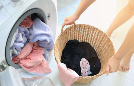 Woman carried a laundry basket in the washing machine and the washing machine is full of clothes that need cleaning.