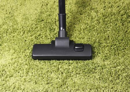 green carpet: Vacuum cleaner head on green carpet