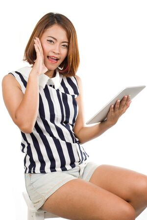 Asian woman sitting of the chair shouting and holding tablet on her hand on White background Banque d'images