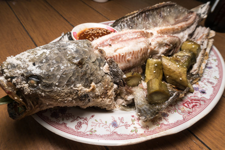 crusted: Salt-Crusted Grilled Fish on wooden table Stock Photo