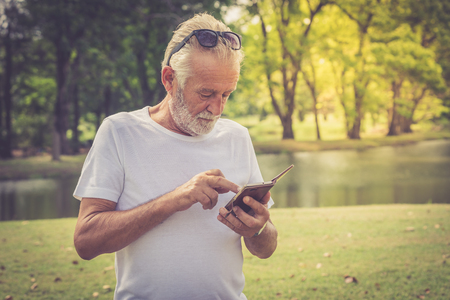 Elderly man standing in the park and using his mobile phone to check message and news
