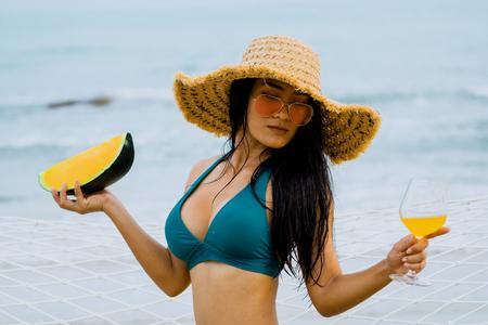 Thai woman in Bikini with straw hat holding water melon and orange juice walking on the beach